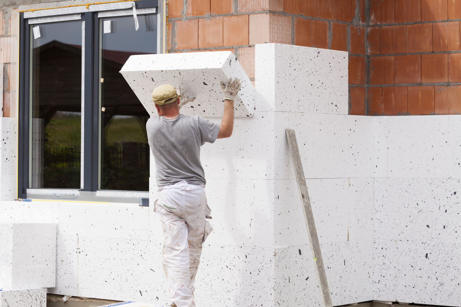 Workers spreading mortar over styrofoam insulation and mesh with